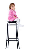 Het meisje zit op een hoge stoel Stock Afbeeldingen