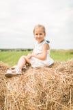 Het meisje zit op een hooiberg, een de zomerconcept Royalty-vrije Stock Afbeeldingen