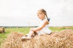 Het meisje zit op een hooiberg, een de zomerconcept Stock Fotografie