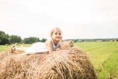 Het meisje zit op een hooiberg, een de zomerconcept Royalty-vrije Stock Fotografie