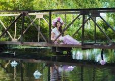 Het meisje zit op een kleine brug in een bloemkroon stock foto's