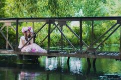 Het meisje zit op een kleine brug in een bloemkroon royalty-vrije stock afbeelding