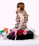 Het meisje zit op een koffer met dingen Stock Afbeelding