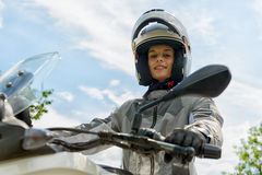 Het meisje zit op een motorfiets en heeft een helm op zijn hoofd royalty-vrije stock foto
