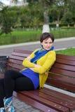 Het meisje zit op een parkbank Royalty-vrije Stock Foto's