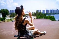 Het meisje zit op een skateboard en is drinkwater op een de zomerdag royalty-vrije stock afbeeldingen