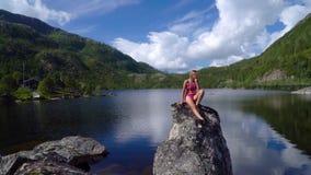 Het meisje zit op een steen dichtbij het meer stock videobeelden