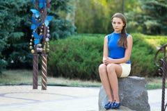 Het meisje zit op een steen in park Stock Fotografie