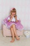 Het meisje zit op een stoel stock afbeeldingen