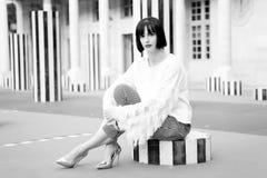Het meisje zit op gestreepte kolom in Parijs, Frankrijk stock foto