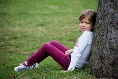 Het meisje zit op het gras dichtbij de boom op weide in de lente Stock Afbeelding