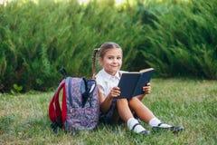 Het meisje zit op het gras en leest boek Leerlingen van lage school Begin van lessen Eerste dag van daling royalty-vrije stock foto