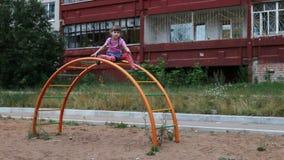 Het meisje zit op halfronde ladder en golvenhand stock videobeelden