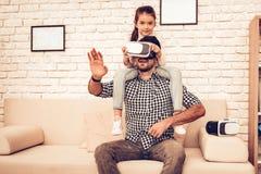 Het meisje zit op Man Hals in Virtuele Werkelijkheidsglazen stock afbeelding