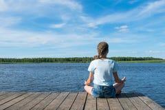 Het meisje zit op het meer en bekijkt de mooie blauwe hemel, mening van de rug royalty-vrije stock foto's