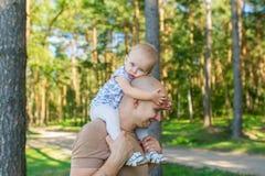 Het meisje zit op schouder bij vader in park in de herfst Royalty-vrije Stock Afbeeldingen