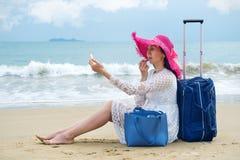 Het meisje zit op strand en schildert lippen met lippenstift stock foto's