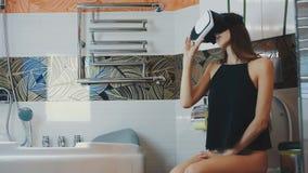 Het meisje zit op toilet in badkamers in virtuele werkelijkheidsglazen spel Rond het kijken stock videobeelden
