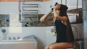 Het meisje zit op toilet Het kijken in virtuele werkelijkheidsglazen Badkamers Virtueel spel stock video