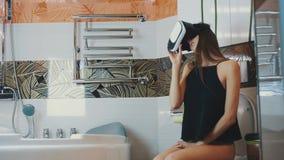 Het meisje zit op toilet Het kijken in virtuele werkelijkheidsglazen Badkamers Virtuele wereld stock video
