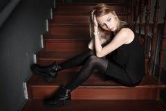 Het meisje zit op treden Stock Foto's