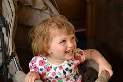 Het meisje zit in wandelwagen en lacht Royalty-vrije Stock Foto's