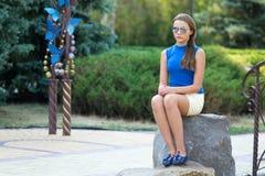 Het meisje in zonglazen en met lang aan haar zit op een steen Royalty-vrije Stock Afbeelding