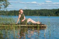 Het meisje zonnebaadt op het dok royalty-vrije stock afbeeldingen