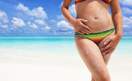 Het meisje zonnebaadt op het strand door de oceaan Stock Foto