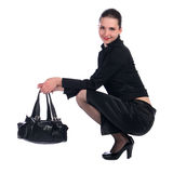 Het meisje in zwart kostuum met zak zit. Royalty-vrije Stock Afbeeldingen