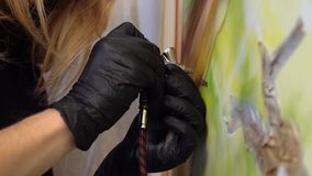Het meisje in zwarte handschoenen trekt op de muur stock videobeelden