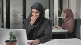Het meisje in zwarte hijab zit in het bureau en de hoest, een ziekte, een koude, een ziekte is een concept Meisje in roze hijab i stock footage