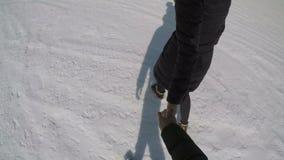 Het meisje in zwarte kleding die een mens vooruit in sneeuw leiden stock video