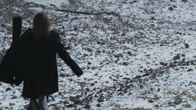 Het meisje in zwarte laag die op sneeuwheuvels lopen stock video