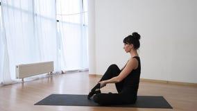 Het meisje in zwarte sportkleding toont rek vooruit haar benen en één voor één bij pilates langzame motie stock videobeelden