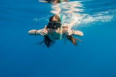 Het meisje in zwemmend masker duikt in Rode overzees stock foto's