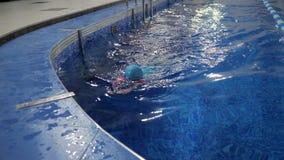 Het meisje in zwempak, GLB en beschermende brillen duikt en zwemt aan egge van pool stock footage