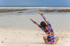 Het meisje in zwempak overhandigt op het zitten bij wit zandstrand royalty-vrije stock foto's