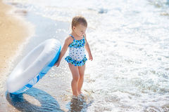 Het meisje zwemt binnen kostuum met zwemmende cirkel klaar om in het overzees bij vroege zonsondergang te gaan Jongen en de meisj royalty-vrije stock afbeelding