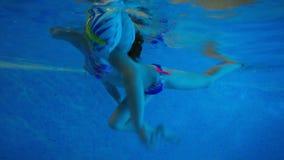Het meisje zwemt in de opblaasbare armbanden stock video