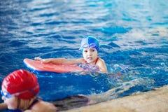 Het meisje zwemt in de pool op het bord stock fotografie
