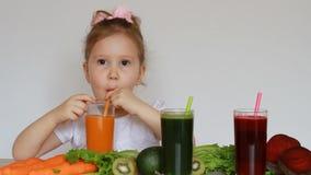 Het meisjekind drinkt plantaardige smoothies - Wortel, biet en groen detox Een leuke baby die een glas met sap houden stock video