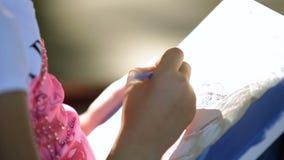 Het meisjekind zit in het park, op een bank en ricott een olie op canvasclose-up stock video