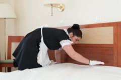 Het meisjemeisje, kleedde zich in zwarte, die deken op bed zetten Royalty-vrije Stock Fotografie