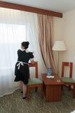Het meisjemeisje, kleedde zich in zwarte, die het schoonmaken procedure maken Stock Foto's