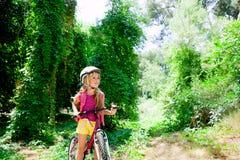 Het meisjes berijdende fiets van kinderen in het bos glimlachen Stock Afbeeldingen