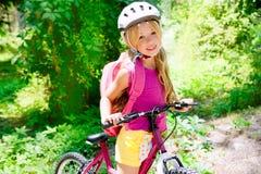 Het meisjes berijdende fiets van kinderen openlucht in bos Royalty-vrije Stock Afbeeldingen