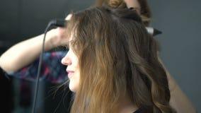 Het meisjes` s haar van kapperdraaien bij het krullen stock footage