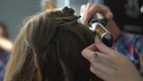 Het meisjes` s haar van kapperdraaien bij het krullen stock video
