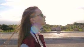 Het meisjesblonde pathetisch en gaat vol vertrouwen langs de weg De mannequin, tiener, zwarte oorringen, juwelen, snakt stock video